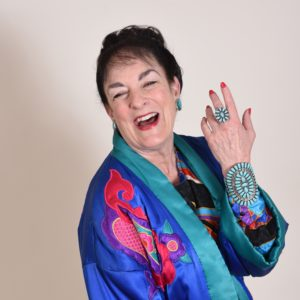 Picture of Nancy Wyatt, Owner, My Persuasive Presentations, LLC, in coat of many colors showing turquoise ring and bracelet created by Native Americans
