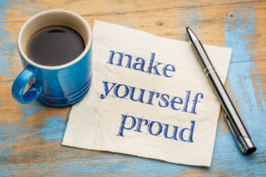 "The words, ""Make yourself proud"" - handwriting on a napkin with a blue cup of espresso coffee"