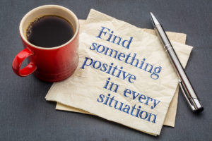 Red cup of coffee on note saying Find something positive in every situation.