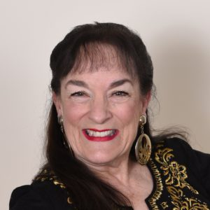Head shot of Nancy Wyatt, composer of HypnoMeditations, dressed in black with gold trim