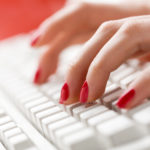 Woman's fingers typing with computer keyboard