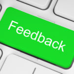 green feedback button on keyboard critiquing a manuscript