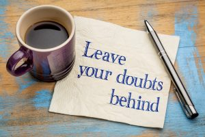 """Leave your doubts behind"" - handwriting on a napkin with a purple cup of espresso coffee"