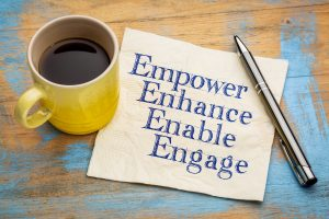 yellow coffee cup and napkin which says - empower, enhance, enable and engage