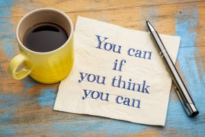 You can if you think you can - inspirational handwriting on a napkin with a yellow cup of coffee