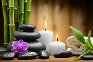 zen basalt stones and orchid with bamboo and white candles on the wood