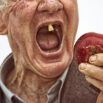 dirty homeless man with one tooth about to take a giant bite of a red apple