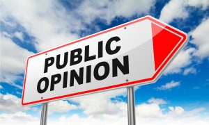 "The words,""Public Opinion""on Red and white Road Sign against a blue sky and puffy white clouds background"