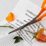 orange-handled scissors cutting divorce papers with orange flower and petals lying on the document