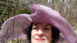 Nancy in big lavender Spring hat against bare tree branches