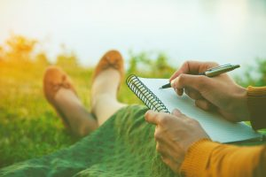 female hands with pen writing on notebook. She's sitting on the grass with a green shawl and gold shoes and sleeve showing.