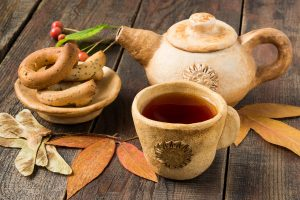 Rustic Tea Party: hot tea in earthenware teapot and cup, autumn leaves and fruits on a wooden table. Selective focus
