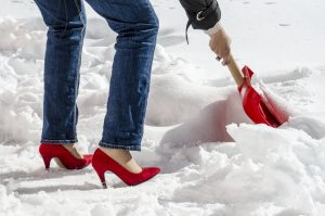 woman in jeans and red high heels shovels snow with a red shovel