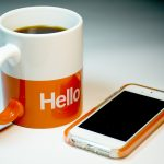 "coffee cup labeled ""hello"" and a smart phone"