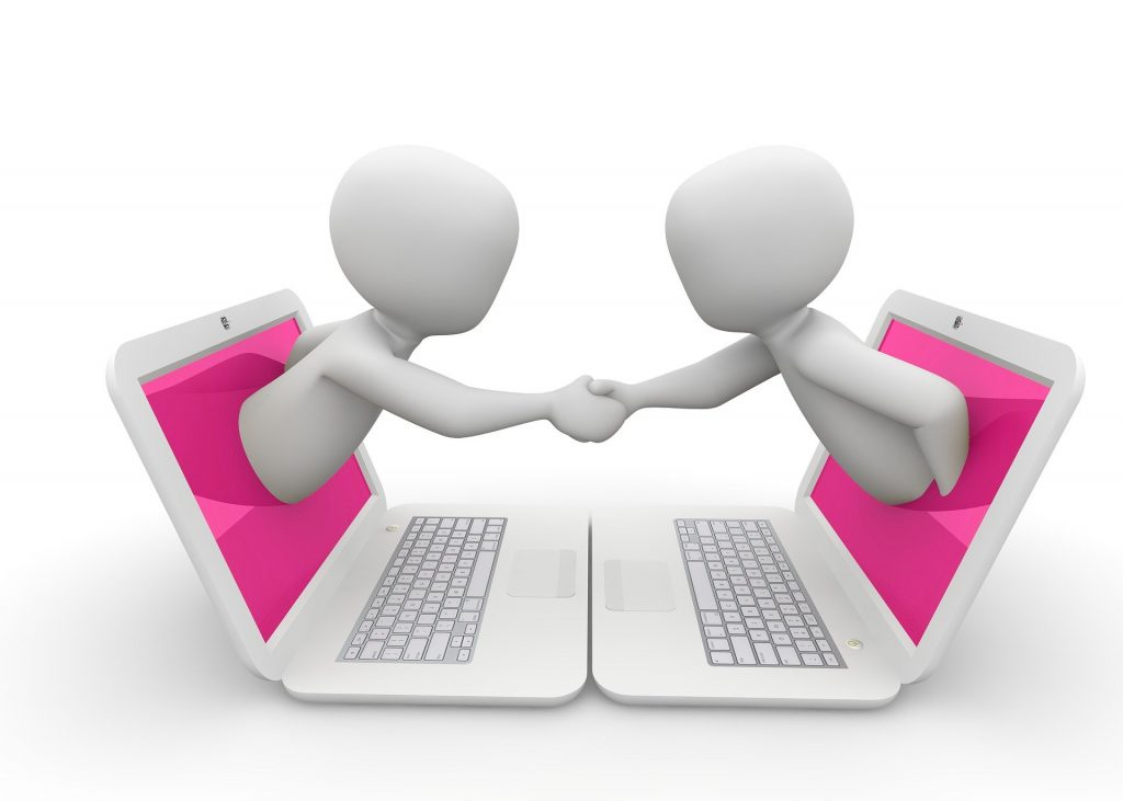 two figures shaking hands from the screens of their laptops