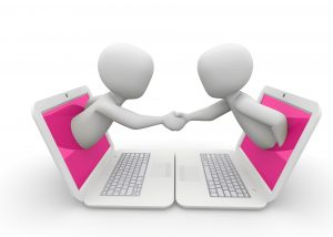 two figures emerging from laptops and shaking hands from the screens of their laptops