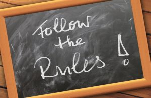 """Black board with chalk writing """"Follow the Rules!"""""""