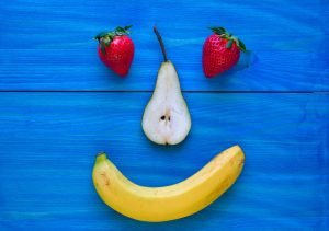 a happy face made of fruit on a blue background