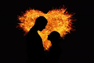 Silhouette of a man and woman facing each other against the background of a heart on fire by Gerd Altmann