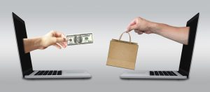 two laptops facing each other - hand with money and hand with shopping bag