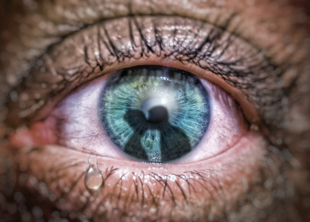 a reddened eye with a tear as it gazes at the reflection of a man and woman kissing