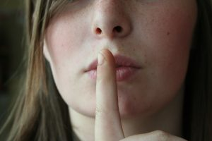 woman with finger to her lips indicating secret or hush