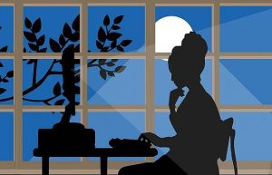 Silhouette of woman working at computer by the light of the full moon.