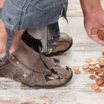 feet in tattered shoes homeless man reaches for coins
