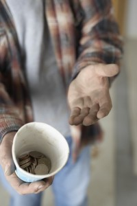 homeless man with cup for change