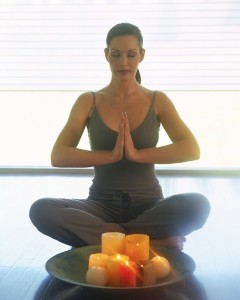 woman meditating on her affirmations with candle and water in classes